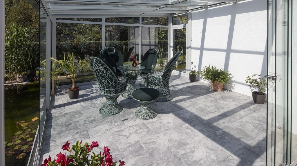 giardino d'inverno con pavimento da esterni simil pietra